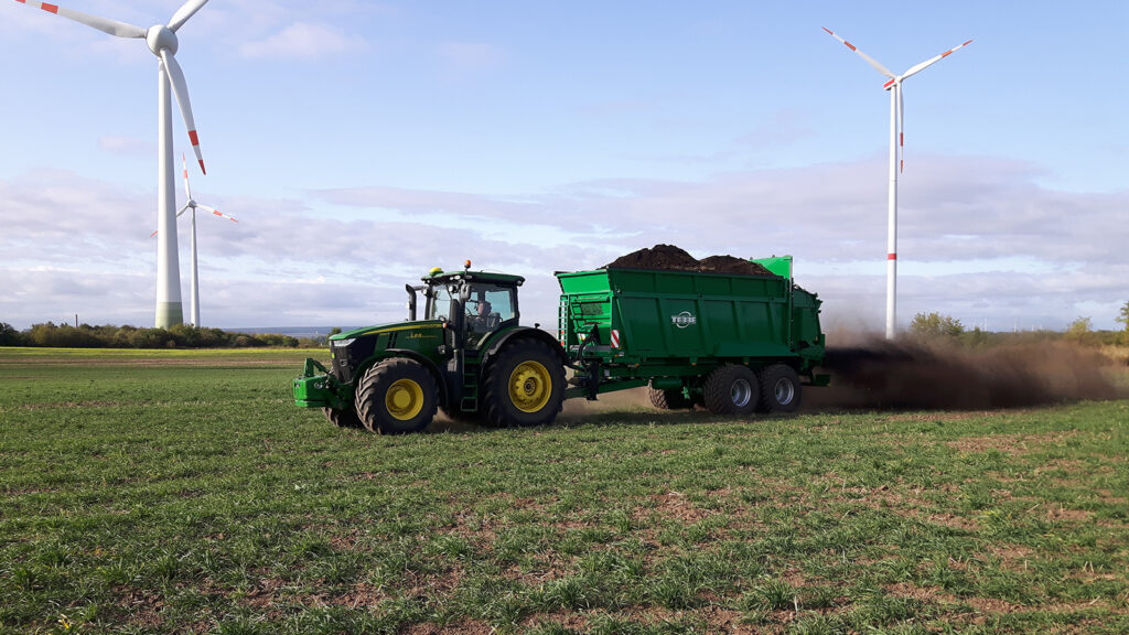 Traktor mit Anhänger bei der Ausbringung von Kompost